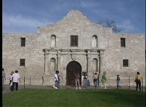 Tourists walk in front of the Alamo Stock Video Footage