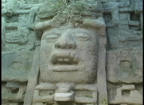 A stone carving of a Mayan face adorns an ancient site in... Stock Video Footage