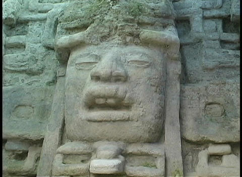 A stone carving of a Mayan face adorns an ancient site in Mexico Footage