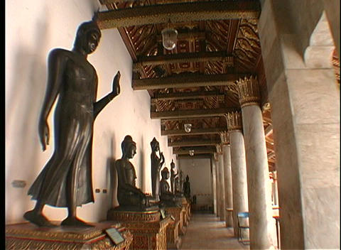 Statues rest against the interior wall of a temple... Stock Video Footage
