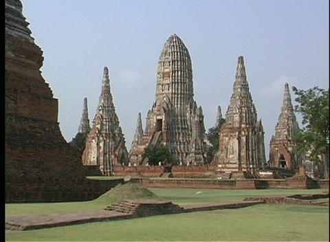 A lush courtyard surrounds the ancient stone temples of Ayutthaya, Thailand Footage