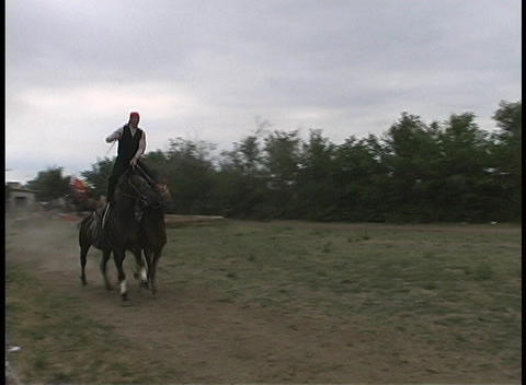 A man balances on two galloping horses as they run down a... Stock Video Footage