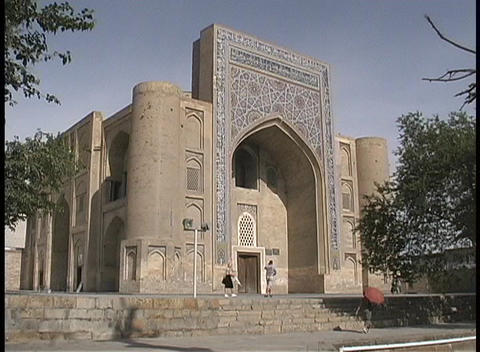 People walk in front of a mosque in Central Asia Stock Video Footage
