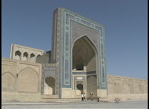 People walk in front of an ancient mosque in Bukhara, Uzbekistan Footage