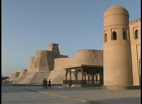 People walk in front of the walled city of Khiva, Uzbekistan Stock Video Footage