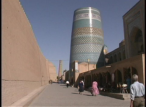 People walk through a short minaret called the Kalta Minor in Khiva, Uzbekistan Footage