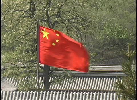 A Chinese flag flies over rooftops on a summer day Stock Video Footage