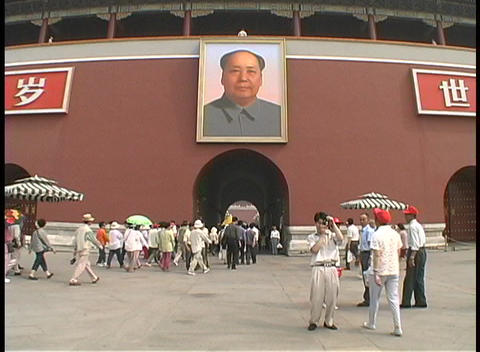 People walk under a portrait of Mao Zedong on the... Stock Video Footage