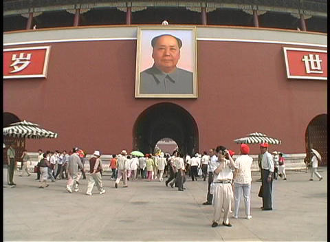 People walk under a portrait of Mao Zedong on the Imperial Palace Footage