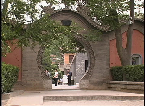 A round gate adorns the entrance to a courtyard in... Stock Video Footage