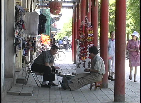 men play a board game outside shops in Dunhuang, China Stock Video Footage
