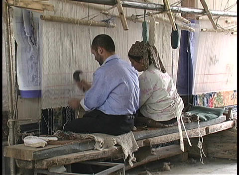 A man and woman work on a loom in Hotan, China Stock Video Footage