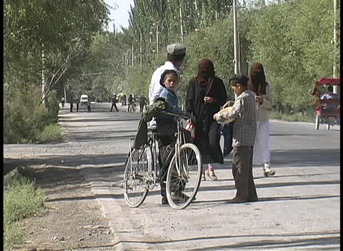 Muslim women in abayas walk by a man on a bicycle with... Stock Video Footage