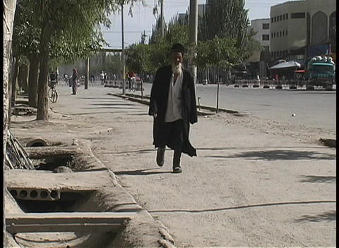 A man in traditional garb walks along a street near... Stock Video Footage