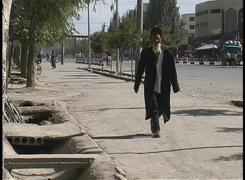 A man in traditional garb walks along a street near Kashgar, China Footage