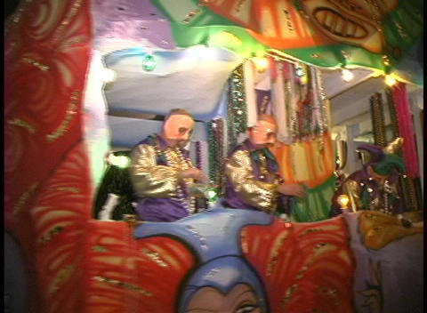 A colorful, flashing float with costumed characters throws beads to the crowds at night during Mardi Footage