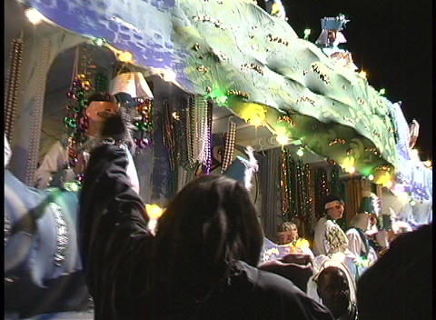 A woman catches a strand of beads thrown by the colorful characters on a Mardi Gras float and then s Footage