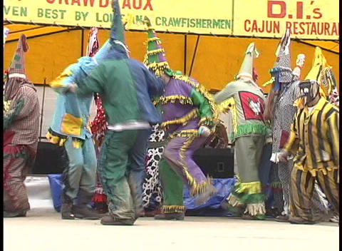 Mardi Gras costumed folks dance outside a tent advertising Mardi Gras sponsors or participants Footage