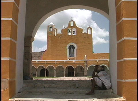 A terracotta colored church is seen across the courtyard... Stock Video Footage