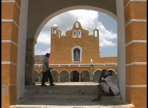 A terracotta colored church is seen across the courtyard of a convent in Izamal, Mexico Footage