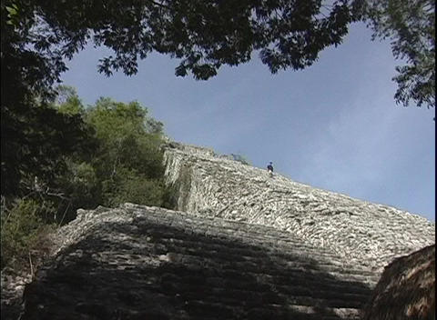 A lone tourist descends the ancient Mayan pyramid in Tulum, Mexico Footage