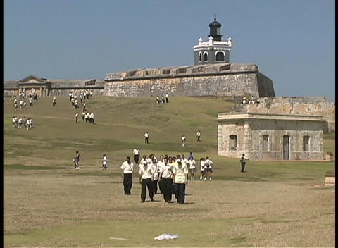 Schoolboys walk down the hill in front of El Moro Fort Stock Video Footage