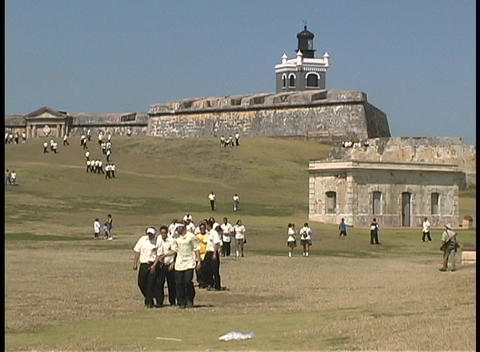 Schoolboys walk down the hill in front of El Moro Fort Footage