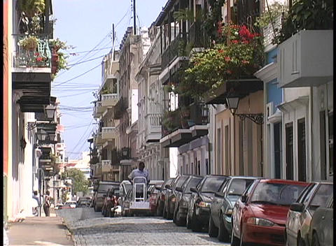 A man pushes a dolly down a picturesque San Juan street... Stock Video Footage