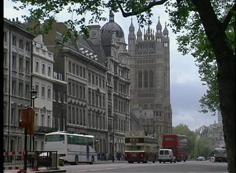 Double decker buses and other automobiles are seen passing Westminster Abbey in London, England Footage