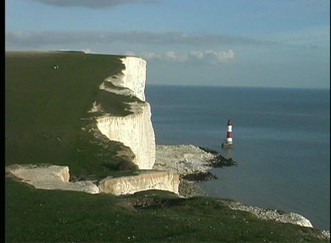 In front of the White Cliffs of Dover, a red and white lighthouse can be seen Footage