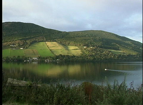Green hillsides are reflected in the glassy surface of Loch Ness Footage
