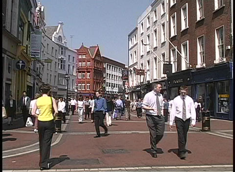Shoppers and pedestrians walk down a main street in Dublin, Ireland Footage