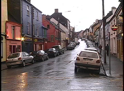 Medium shot of businesses along a rainy street in Dingle, Ireland Footage