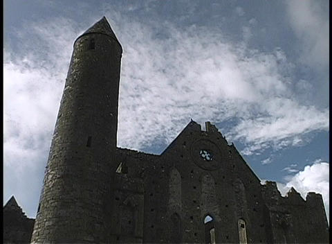 Birds fly over the Clonmacnoise Tower in Ireland Footage