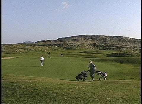 Golfers prepare to putt on the green at County Sligo Ireland Stock Video Footage