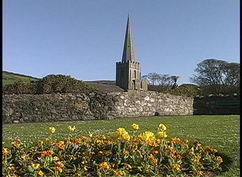 The spire of a cathedral towers over a colorful garder near Struell Wells Ireland Footage