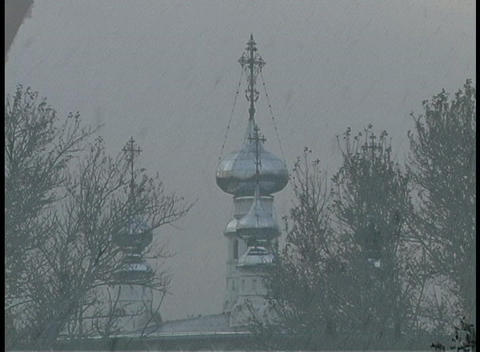 A golden-hour shot of snow falling on the steeple of the Russian Orthodox Christian Church in Russia Footage