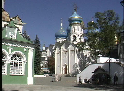 A pan shot of people walking toward the Sergiev Posad Church in Russia Footage