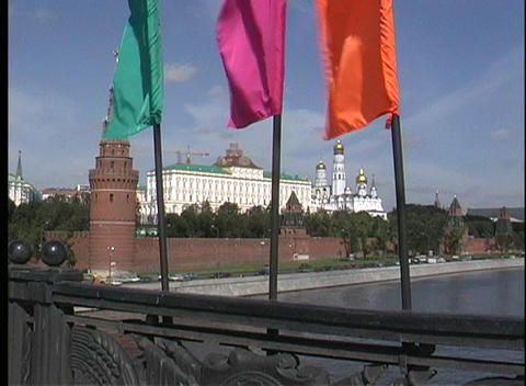 Colorful flags wave in the breeze with the Moscow River in the foreground of the Kremlin in Russia Footage