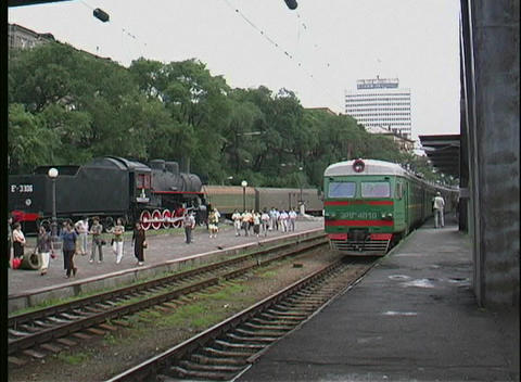 A green trans Siberian railway passenger train pulls into a Russian station Footage