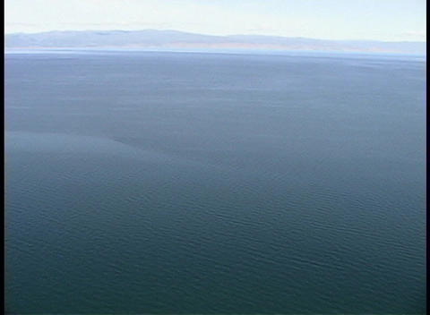 A pan-left of an ocean, viewed from the edge of a steep... Stock Video Footage