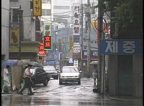 Pedestrians and traffic travel through a rainy... Stock Video Footage