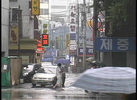Pedestrians and traffic travel through a rainy intersection in Seoul, South Korea Footage