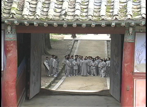 A group of Buddhist monks wait in the courtyard at the... Stock Video Footage