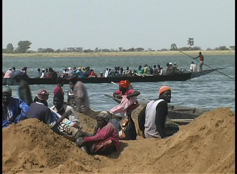 Pan across long boats on the Niger River, with people... Stock Video Footage