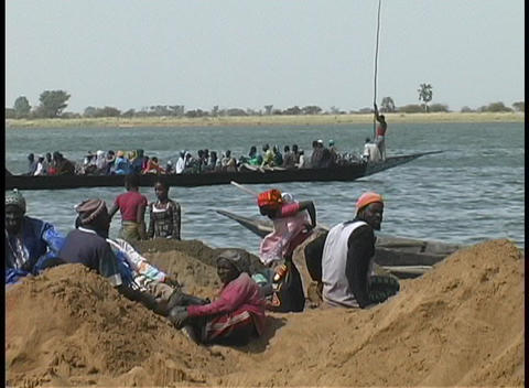 Pan across long boats on the Niger River, with people talk and waiting in the foreground Footage