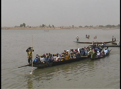 A long ferryboat carries passengers along the shore of the Niger River Footage