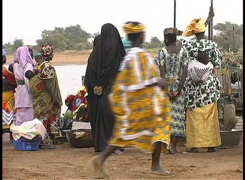 A medium-shot of people gathering along the street for an open market in Mali Footage