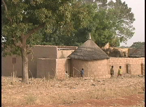 A medium shot of children playing outside the mud huts of... Stock Video Footage