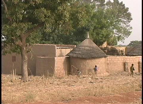 A medium shot of children playing outside the mud huts of Dogon Village in Mali, West Africa Footage